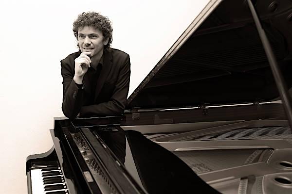 Roberto Olzer posa appoggianto su un pianoforte a coda nero